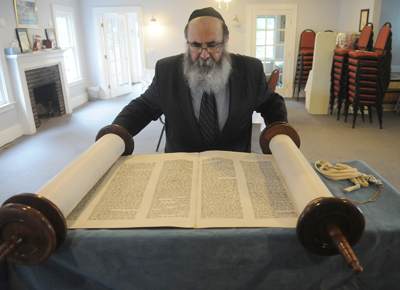 (RNS1-JUNE08)  Rabbi Yaakov Rapoport unrolls the Torah scrolls at the Chabad House near Syracuse University, which has applied for $61,876 in federal security grants to install blast-resistant windows, security cameras and other improvements.For use with RNS-SECURITY-GRANTS, transmitted June 8, 2009. Religion News Service photo by Stephen D. Cannerelli / The Post-Standard.