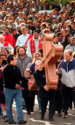 (RNS) Followed by more than 1,500 Good Friday worshippers in 2000, Jessie Rodriguez carries a cross that once stood atop Sacred Heart Church in Aurora, Ill. The scene is part of a ``Way of the Cross,'' or Via Crucis, procession that re-enacts and commemorates the march of Jesus to his crucifixion. Religion News Service file photo by Steven Buyansky/The Beacon News.