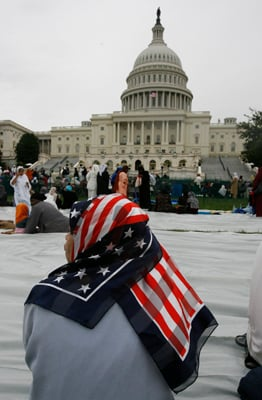 """(RNS) A woman with a patriotic head scarf sits in front of the US Capitol during a 2009 """"Islam on Capitol Hill' event. Muslim leaders are now concerned about planned House hearings on the """"radicalization of American Muslims."""" RNS file photo by Tim Farrell/The Star-Ledger."""