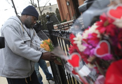 Michael Nash of Newark, N.J., leaves flowers at  a make-shift memorial outside the New Hope Baptist Church, where singer Whitney Houston honed her talents in the choir.