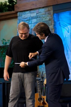 """Dr. Mehmet Oz measures megachurch pastor Rick Warren's waisteline at a """"Daniel Plan"""" forum at Saddleback Church in Lake Forest, Calif. Warren has already lost 60 pounds, and hopes to lose 30 more using the faith-based diet plan. RNS photo courtesy Toby Crabtree/Saddleback Church"""