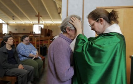 Duke Divinity School professor and author Lauren Winner prays with Frances Sheve, center, during services at St. Luke's Episcopal Church in Durham, NC.