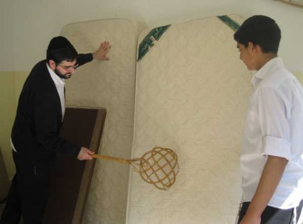 Two Orthodox Jewish Jerusalemites clean their mattresses ahead of the Passover holiday.