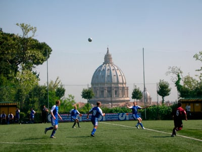 Members of the Pontifical North American College soccer team (in blue) play the Pontifical Gregorian University in Rome in 2007, with St. Peter's Basilica in the background. The teams  are participants in the Clericus Cup, which lost its Vatican-sponsorship.