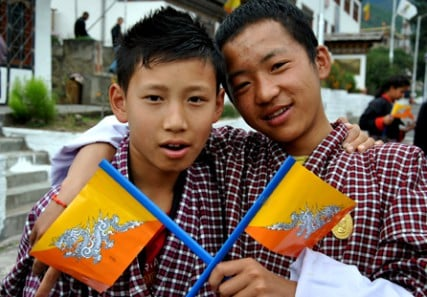 Two Bhatanese students carry the national flag as they await the arrival of the country's king and queen in the capital city of Thimphu.