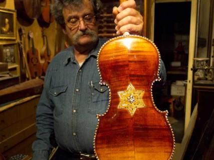 Amnon Weinstein holds a Kelzmer violin.