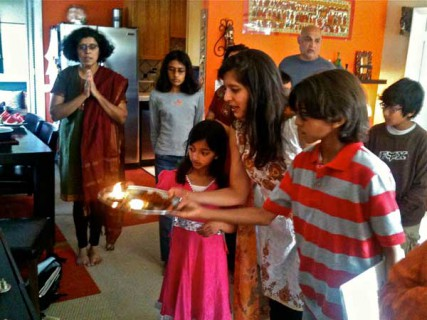 Mudita Bahadur performs an offering with her children, Nadeen, 11, and Nikita, 9, before the Bal Kendra group breaks for social hour.