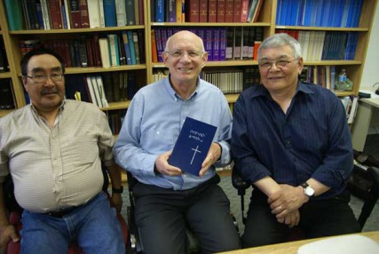 Inuktitut Bible translators Jonas Allooloo (left) and Benjamin Arreak (right) flank Hart Wiens, director of scripture translation for the Canadian Bible Society, who holds a copy of the New Testament in Inuktitut.