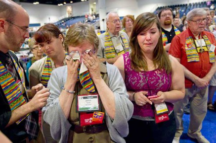 Delegate Jo Ann Carlotto (second from left) of the New England Conference wipes her eyes with a rainbow stole after delegates voted to maintain the United Methodist Church's stance on sexuality during the denomination's at 2012 General Conference in Tampa, Fla.