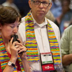 Delegate Sara Ann Swenson (left) of Minnesota presses her voting keypad to her lips while awaiting results of a vote on the United Methodist Church's stance on sexuality during the denomination's 2012 General Conference in Tampa, Fla. At center is fellow delegate the Rev. Bruce Robins. Photo by Mike DuBose/courtesy United Methodist News Service