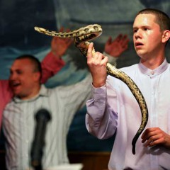 """Andrew Hamblin, 21, pastor of Tabernacle Church of God in LaFollette, Tenn., looks into the eyes of a rattlesnake at the church alter while others sing songs during church service on April 13, 2012. Hamlin is part of a new generation of serpent handling Christian, a 100-year old faith tradition in Tennessee. Since the early 1900s, a handful of true believers in East Tennessee and other parts of Appalachia have practiced the so-called signs of the gospel, found in a little-known passage in the King James Version of the Gospel of Mark: """"And these signs shall follow them that believe; In my name shall they cast out devils; they shall speak with new tongues; They shall take up serpents; and if they drink any deadly thing, it shall not hurt them; they shall lay hands on the sick, and they shall recover."""" While other churches ignore this passage or treat it metaphorically, serpent handlers follow it literally. Their intense faith demands sinless living and rewards them with spiritual ecstasy in the chance to hold life and death in their hands."""