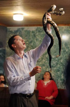 Andrew Hamblin, 21, pastor of Tabernacle Church of God in La Follette, Tenn., holds up two rattlesnakes during church service. For more than a 100 years, small Pentecostal churches in East Tennessee and other parts of Appalachia have handled poisonous snakes and drunk strychnine during their services. The snake handlers say that the Bible tells them to do so, but it's illegal and has mostly died out.