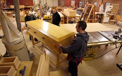 Abbot Justin Brown looks on as Novices Joseph Eichorn, left and Dustin Bernard move a handmade wooden casket through the woodwork shop on the grounds of St. Joseph Abbey outside of Covington, La.