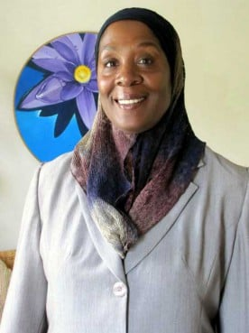 Shahada Sharelle Abdul Haqq, artist. The acrylic on canvas painting behind her is one of her works.