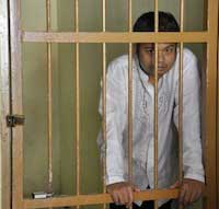 The atheist community has embraced the cause of an Indonesian man, Alexander Aan (pictured here behind bars), who was beaten and jailed after denying God's existence on Facebook and posting cartoons of the Prophet Muhammad.