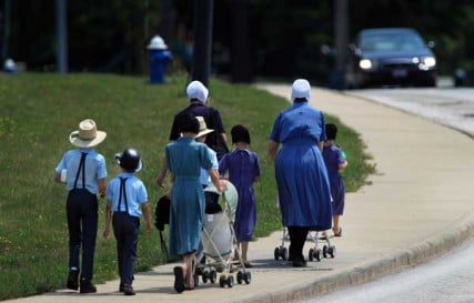 An Amish family walks on Springdale Ave. after visiting the Harrington Square shopping plaza in Middlefield August 2, 2012.