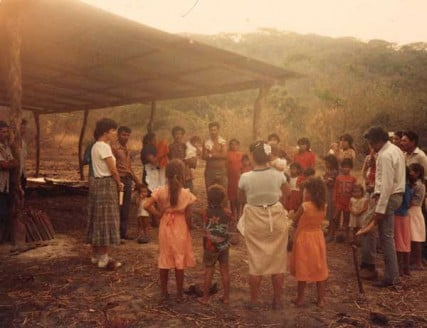 Sister Pat Farrell (far left) gathering a handful of newly arrived displaced people repopulating El Sitio, in the area of Suchitoto, El Salvador 1988.