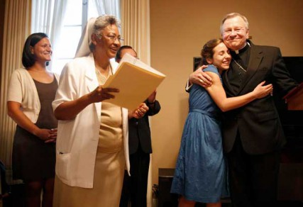 Paige LaCour, second from right, hugs Archbishop Gregory Aymond, right, during the opening of the Magnificat House of Discernment for Women in New Orleans, Louisiana, Wednesday, August 15, 2012. It was a conversation the archbishop had with LaCour that began the idea for the Magnificat House of Discernment for Women.