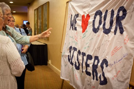 Attendees admire a 'We (heart) Our Sisters' sign hanging outside of the Leadership Conference of Women Religious in St. Louis, Mo. on Friday, August 10, 2012.