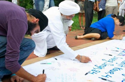 Attendees sign a banner during the prayer vigil for the victims of the Oak Creek Sikh temple shooting on Wednesday evening, August 8, in Lafayette Park in view of the White House.