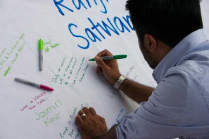 Khuram Zaman signs a banner during the prayer vigil for the victims of the Oak Creek Sikh temple shooting on Wednesday evening, August 8, in Lafayette Park in view of the White House.