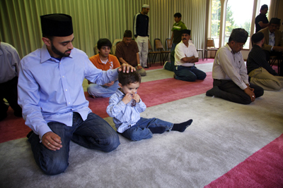 Harris Zafar and his son, Rohan, 2, participate in the Friday prayer service at the Rizwan Mosque in Portland, Ore.. Ahmadiyya is a Muslim sect which emphasizes peace and is a target for persecution in Pakistan.