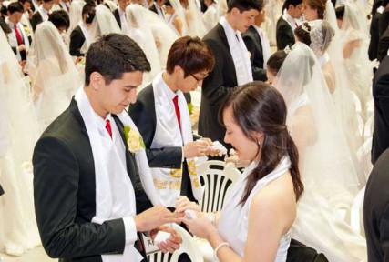 A couple exchanges rings during a mass wedding ceremony arranged by the Unification Church in Korea on March 24, 2012.