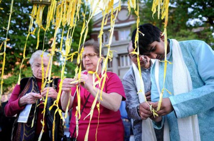Performers and audience members join in attaching ribbons, some with thoughts and prayers written on them, to a peace weaving installation on Washington Boulevard after the Second Annual September 11th Interfaith Memorial in Music at The Sheldon Concert Hall in St. Louis Sunday Sept. 9, 2012. The event, which brought together performers from Christian, Jewish, Muslim, Hindu and Sikh traditions, will be broadcast on HEC-TV on Sept. 11, 17 and 22.