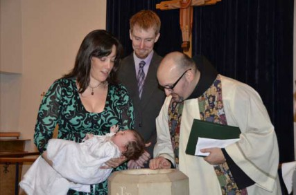 Father Jason Lody baptizes a young member of Fairfax, Va.'s St. Anthony of Padua church.