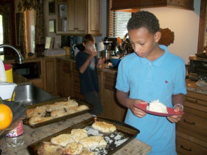 Isaiah Frisch (front) and Mekail Frisch get their Sunday buffet-style lunch in the Frisch family's Toledo home. Their mother Jackie cooked the breaded pork chops but was too ill to join the family for the meal on a recent visit. She suffers from Ehrlers-Danlos Syndrome, which affects the connective tissue and has caused five major strokes.