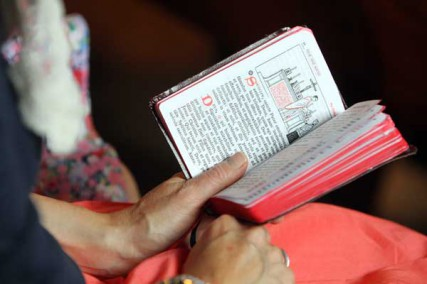 A woman uses a missal during a traditional Latin Mass at St. Michael the Archangel Chapel in Farmingville, N.Y., on June 17, 2012. The chapel is administered by the Society of St. Pius X. RNS photo by Gregory A. Shemitz