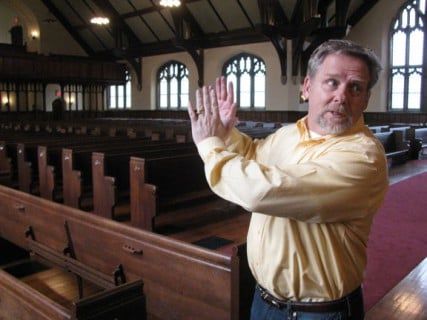 Jerry Patengale, who was hired by the Green family to help find a new owner of a college campus in Northfield, Mass., points out the stone chapel that was once deemed unsafe but has been repaired.