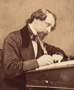 Charles Dickens writing at his desk in 1858.
