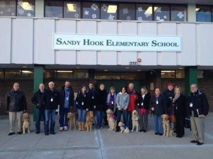 Comfort dogs line up with their handlers outside the new Sandy Hook Elementary school.  RNS photo courtesy Lutheran Church Charities. *Note: This image is not available to download.