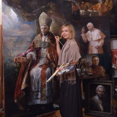 As the popes' official painter, Natalia Tsarkova says she tries to capture both the physical reality and the spiritual essence of her subjects.  Tsarkova is pictured here in front of her portrait of Pope Benedict XVI.  RNS photo courtesy Natalia Tsarkova.