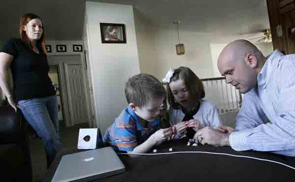 (RNS) Kylee Duff, left, watches two of her children, Jonah, 5, and Mikell, 7, play with her husband Matt before Matt takes them to church, Sunday, February 3, 2013. The Duffs were married in the temple and living happy, Mormon lives until about this time last year, when Matt began to question his faith.  RNS photo by Scott Sommerdorf/The Salt Lake Tribune