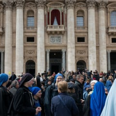 Members of the Catholic community gather in front of St. Peter's basilica after mass during the first day of the conclave on March 12, 2013 at the Vatican. Once announced, the new pope will step out onto the balcony above them. RNS photo by Andrea Sabbadini