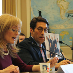 Katrina Lantos Swett, chair of the U.S. Commission on International Religious Freedom, testifies March 15, 2013 on Capitol Hill and holds up a photo of Baha'i leaders who have been sentenced in Iran to 20 years in prison. To her left is Jay Sekulow, chief counsel of the American Center for Law and Justice, who urged the release of Iranian-American minister Saeed Abedini from a Tehran prison. RNS photo by Adelle M. Banks