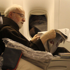 The Archbishop of Boston Cardinal Seán O'Malley, OFM, Cap. catches up on the news aboard a flight to Rome on Tuesday, February 26, 2013. Cardinal O'Malley will be joining his fellow cardinals for a meeting with the Holy Father, Pope Benedict XVI on Thursday, February 28, 2013. RNS photo by Gregory L. Tracy, The Pilot.