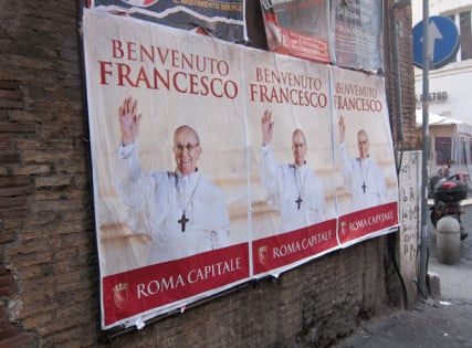 Signs line a wall in Rome welcoming Pope Frances. RNS photo by David Gibson