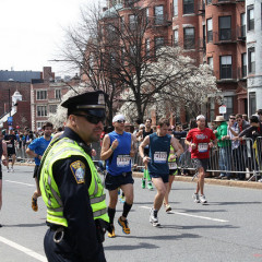 A Police officer stands by as runners pass during the 2013 Boston Marathon.  Photo courtesy Sonia Su via Flickr (http://flic.kr/p/ebzEmM)