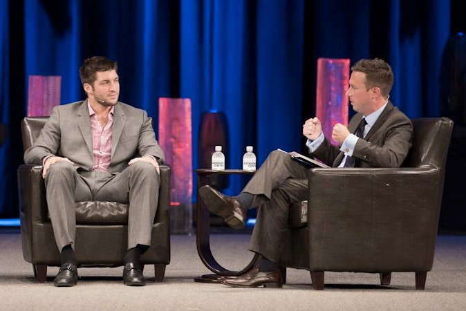 Radio host and author Ken Coleman interviews NFL quarterback Tim Tebow