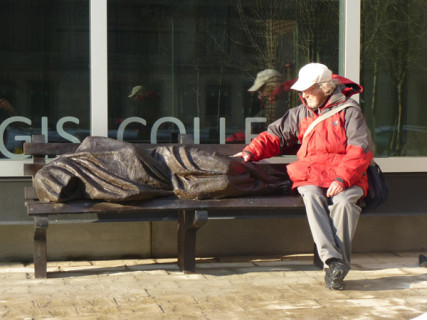 "Peter Larisey seated alongside the Jesus sculpture. Canadian sculptor Timothy Schmalz notes the ironies in his latest creation, ""Jesus the Homeless,"" a bronze sculpture depicting the Christian savior huddled beneath a blanket on an actual-size park bench. Only the feet are visible, and their gaping nail wounds reveal the subject. Photo courtesy Timothy Schmalz"