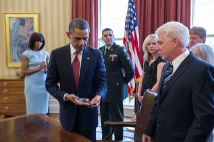 President Barack Obama holds Chaplain (Captain) Emil Kapaun's Easter stole in the Oval Office during a greet with Kapaun's family in the Oval Office, April 11, 2013. The President and First Lady Michelle Obama met with members of Chaplain Kapaun's family before awarding him the Medal of Honor  posthumously during a ceremony in the East Room. Official White House Photo by Pete Souza