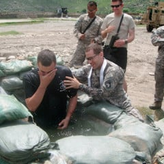 Army Chaplain Capt. Joseph Odell baptizes a fellow soldier on the field in Afghanistan. RNS photo courtesy Joseph Odell