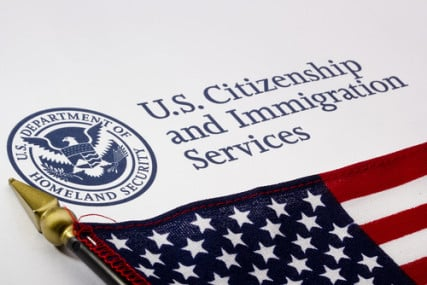 Photograph of a U.S Citizenship and Immigration Services logo and flag courtesy Shutterstock.