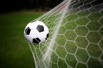 A soccer ball in a goal.