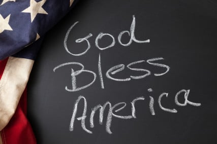 God Bless America sign on a chalkboard with vintage American flag image courtesy Shutterstock