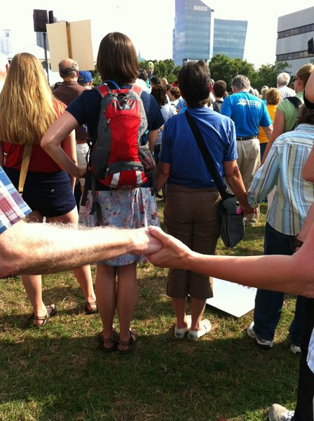 Participants hold hands at the Moral Monday demonstration on the grassy lawn of the N.C. General Assembly last Monday (June 17). During Moral Monday demonstrations, participants listen to a fiery speech denouncing the Republican majority's legislative actions, sing freedom songs, chant civil rights slogans and then they march two by two into the legislative building to be handcuffed by police and arrested for failing orders to disperse. RNS photo by Yonat Shimron