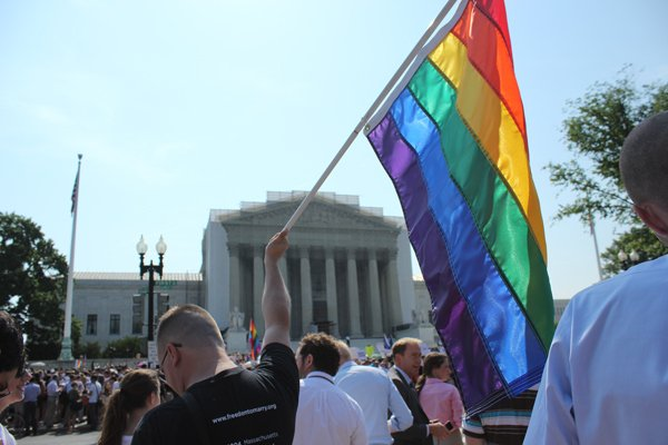 A man holds a gay pride flag in front of the Supreme Court on Wednesday (June26) after the court decided to strike down the Defense of Marriage Act.  RNS photo by Adelle M. Banks